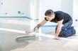 Leinwanddruck Bild - Bodenleger arbeitet mit selbstnivellierendem Zementmörtel.