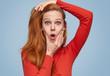 Expressive girl making grimace on blue background