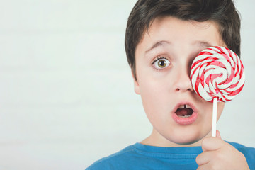 Portrait of child covering eye with lollipop