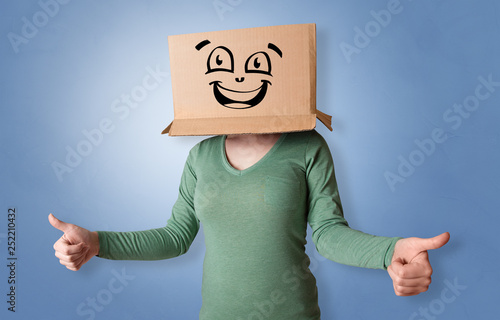Leinwanddruck Bild Young woman with happy face illustrated cardboard box on her head