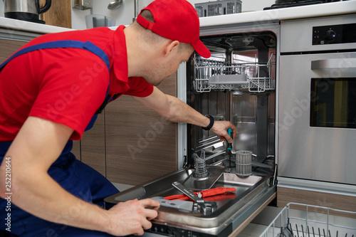 home appliance maintenance - repairman repairing dishwasher in kitchen