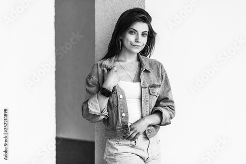 obraz PCV Black and white portrait of beautiful brunette young woman in casual style standing and leaning on wall, standing, holding her denim jacket and looking at camera, smiling. outdoor, summer day time.
