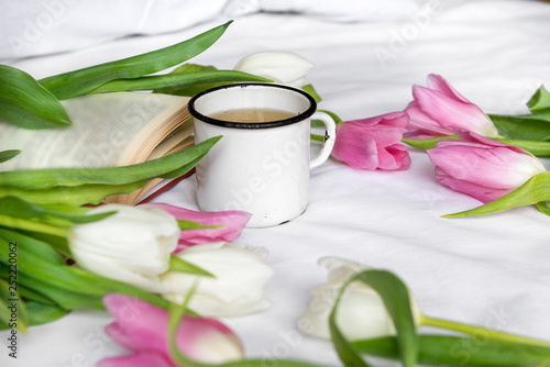 mug, tea, white and pink tulips, a book on a white sheet