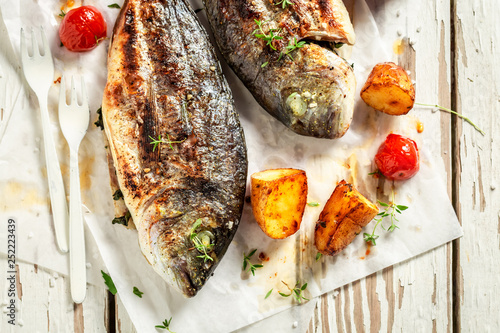 Homemade potatoes and seabream with tomatoes on white table