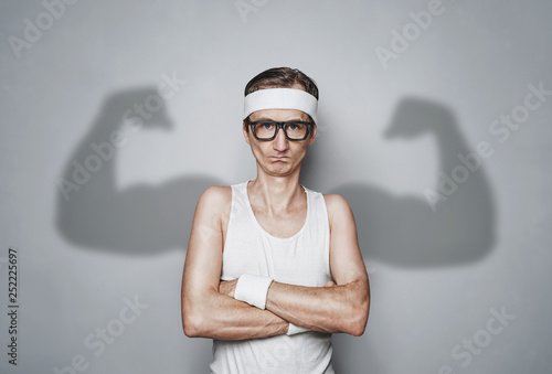 Leinwandbild Motiv Funny sport nerd with shadow muscle arms over gray wall with copy space
