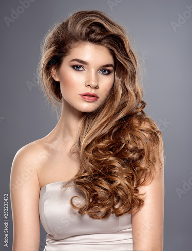 Young brown-haired woman with long curly hair.