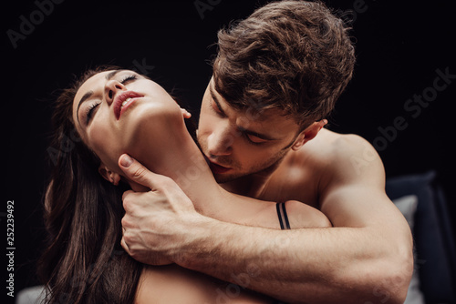 man kissing beautiful sexy woman on neck isolated on black
