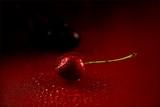 rote Kirsche mit wassertröpfchen auf rotem Untergrund