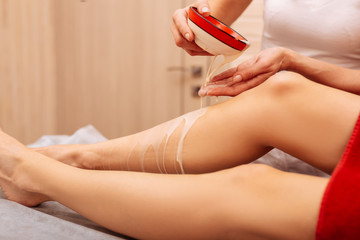 Master in white uniform covering legs of her client with cosmetic liquid