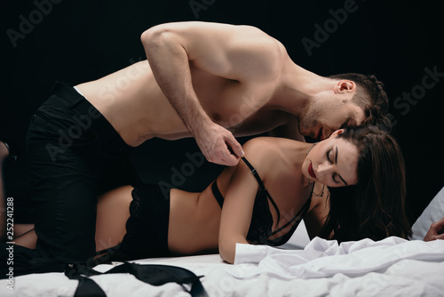 Leinwandbild Motiv man kissing and undressing beautiful sexy woman isolated on black