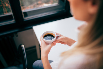 Image of a woman holding a cup of coffee, over the shouder view, focus on the cup.