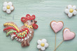 Gingerbreads shaped as a rooster bird and spring flowers on light textured wood