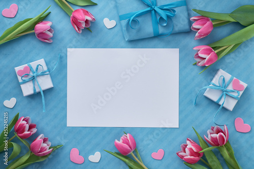 Springtime flat lay with giift boxes, pink tulips and decorative hearts, copy-space
