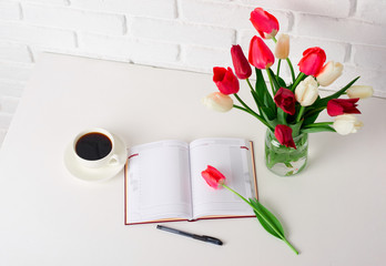tulip flowers are in a vase on the table, cup of coffee and diary, white brick wall as background