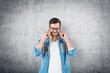 Leinwanddruck Bild - Man in glasses covering his ears, concrete