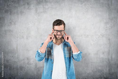 Leinwanddruck Bild Man in glasses covering his ears, concrete