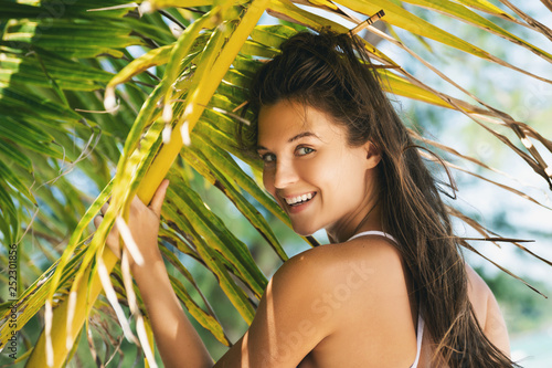 Leinwanddruck Bild Young sexy woman is wearing bikini  posing under palm leaf tree
