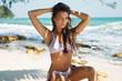 Leinwandbild Motiv Young sexy woman is wearing bikini  posing in the shadow of a palm tree