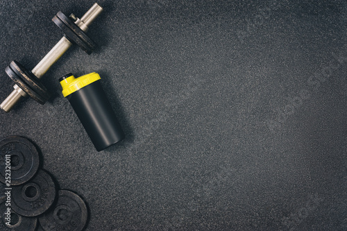 Fitness or bodybuilding concept background. Product photograph of old iron dumbbells on black grey, conrete floor in the gym. Photograph taken from above, top view with lots of copy space - 252320011