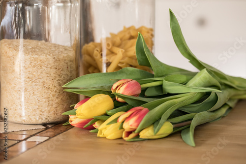 Rice, pasta and a bouquet of tulips on a wooden table in a kitchen, background white Showcase