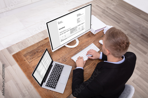 obraz lub plakat Smiling Businessman Checking Invoice On Computer