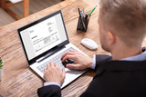 Businessman Checking Invoice On Laptop