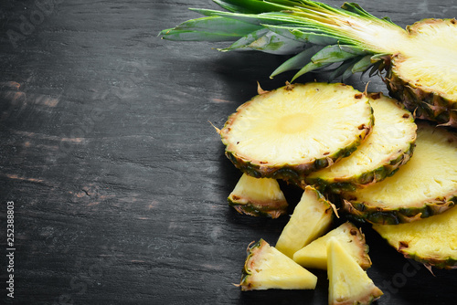 Leinwanddruck Bild Pineapple. Sliced pineapple on a wooden background. Top view. Free copy space.