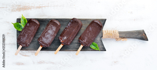 Chocolate ice cream on a stick. On a white wooden background. Top view. Free copy space.