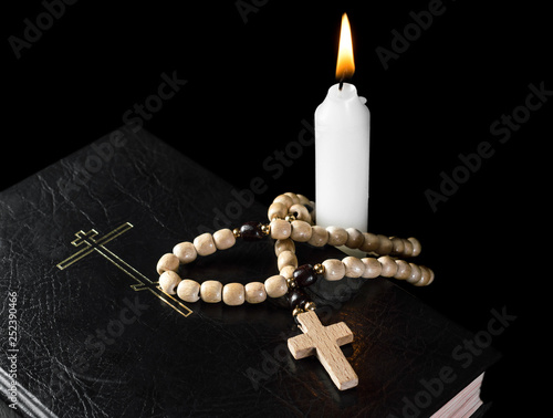 Holy Bible with rosary beads and burning candle on black. Religion concept and faith.