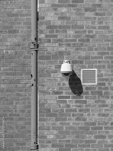 black and white security camera on the brick wall - 252406674