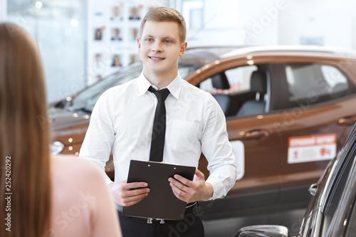 Leinwandbild Motiv Young couple choosing a car with salesman at the dealership