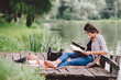 Leinwandbild Motiv Learning / reading woman concept at summer lake