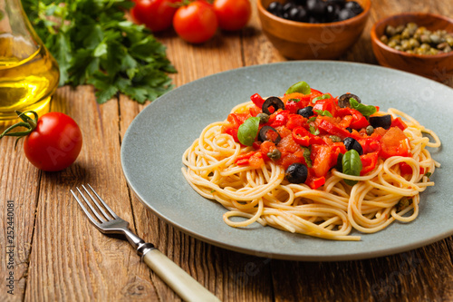 Leinwanddruck Bild Italian spaghetti alla Pultanesca with tomatoes and olives. Served without meat and cheese.