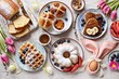 Leinwandbild Motiv Easter festive dessert table with hot cross buns, cakes, waffles and pancakes. Overhead view
