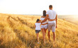 Happy family walking in nature at sunset in summer.