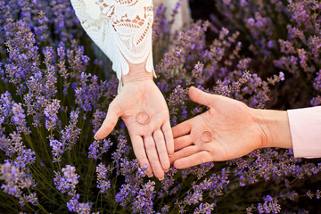 Wedding rings on hands in the field of lavender.