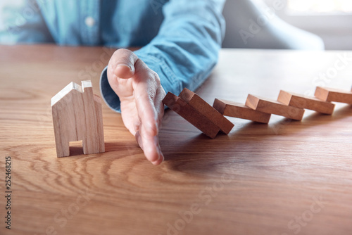 Leinwandbild Motiv Woman hand stopping risk the wooden blocks from falling on house, Home insurance and security concept.