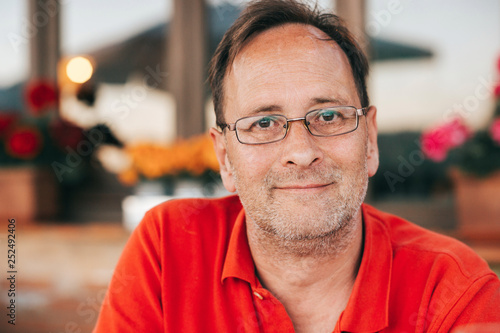 Leinwandbild Motiv Outdoor portrait of 50 year old man wearing red polo shirt and eyeglasses