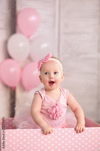 happy little year old girl in pink tutu skirt and leggings with balloons
