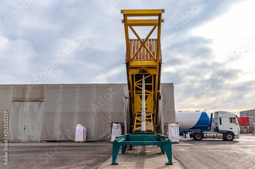 Contenedor descargando levantado sobre plataforma realizando operaciones de trasvase para cargar camión silo cisterna en puerto seco