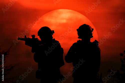 Silhouette illustration of two soldier in front of the big sun. © next143