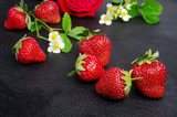 Ripe strawberries with flowers and leaves on a dark background
