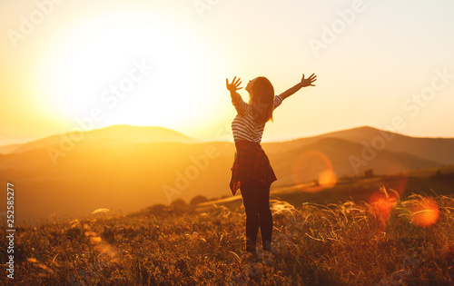 Leinwanddruck Bild Happy woman jumping and enjoying life  at sunset in mountains.