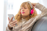 adult woman in the sofa with headphones and phone