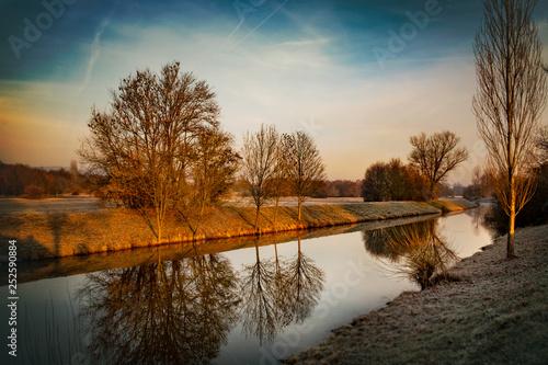 Leinwanddruck Bild stiller Fluss mit spiegelnden Bäumen