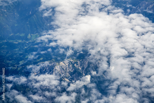 View of the Earth from the airplane flying above the clouds at high altitude over the mountains. Selective Focus - 252596682