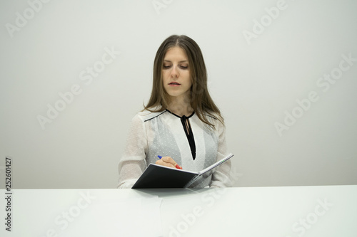 obraz lub plakat A young brunette girl with her hair straight sits at the table with a notebook in her hands, holding a pen in her hand, carefully and seriously writes in the diary