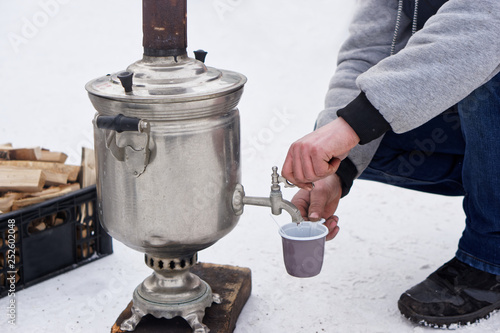 A man pours boiling water from a samovar during a winter picnic © slexp880