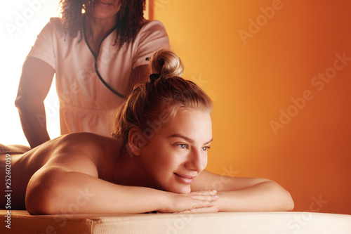 Leinwanddruck Bild Beautiful authentic female masseur doing professional therapeutic massage to a young woman. Spa treatments, back therapy