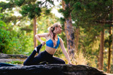 Blonde woman doing quad stretching sitting exercises outdoors on a rock in the forest. Yoga nature concept.